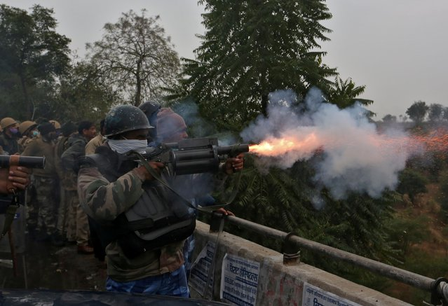A member of the Rapid Action Force (RAF) fires a tear gas shell towards farmers as they try to cross barricades during a protest against newly passed farm laws on a highway at Dharuhera in the northern state of Haryana, India, January 3, 2021. (Photo by Prashant Waydande/Reuters)