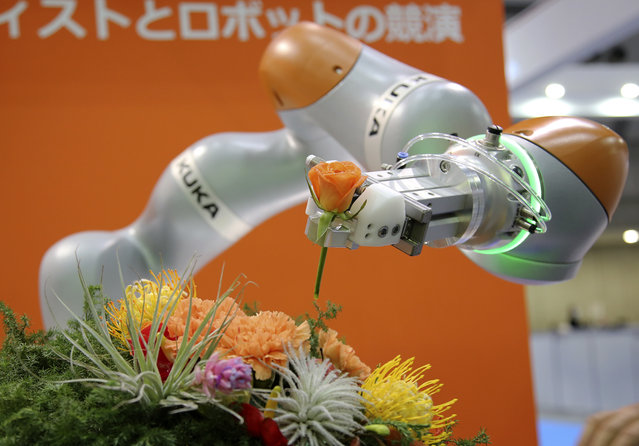 German KUKA Robotics' robot LBR iiwa demonstrates a flower arrangement at the International Robot exhibition in Tokyo, Wednesday, December 2, 2015. (Photo by Shizuo Kambayashi/AP Photo)