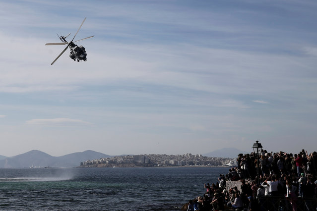 Spectators watch a Super Puma helicopter operating in a mock Search and Rescue operation, during a show marking the Hellenic Air Force's Patron Saint celebration, on the southern suburb of Faliro, in Athens, Greece, November 6, 2016. (Photo by Alkis Konstantinidis/Reuters)