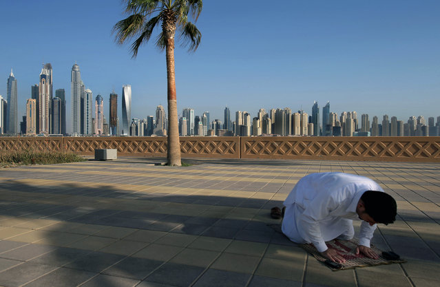 In this April 6, 2015 photo, with the Marina skyline as a backdrop, a Muslim man performs the afternoon prayer on Jumeirah Palm Island's walkway, in Dubai, United Arab Emirates. High-rise buildings, stacked row after row, make up this 50 million sq. foot (4.65 million sq .meter) waterfront neighborhood that is built around a man-made canal where the wealthy park their yachts. To mark its place in the world, the Dubai Marina boasts the world's tallest residential building. (Photo by Kamran Jebreili/AP Photo)