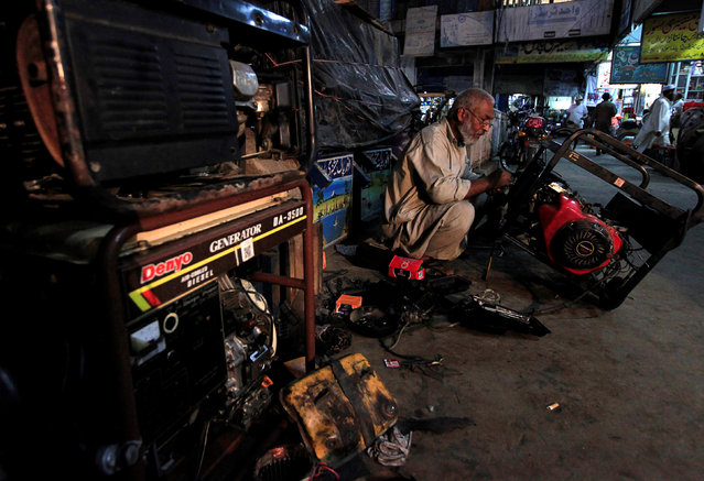 A generator mechanic works outside his shop in Rawalpindi, Pakistan, October 8, 2016. (Photo by Faisal Mahmood/Reuters)