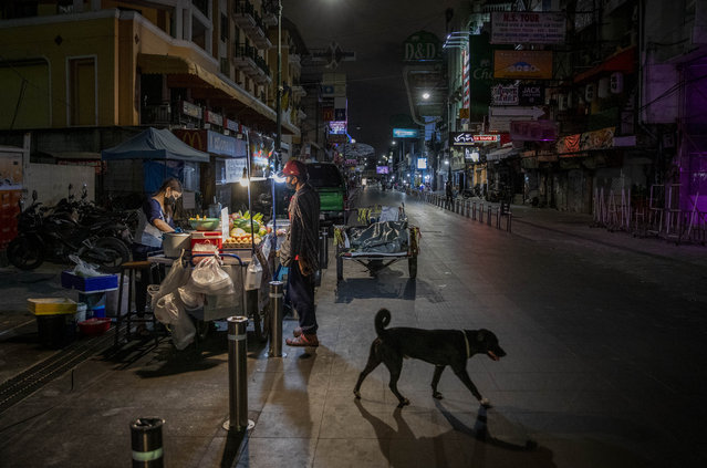 In this January 4, 2021, file photo, a lone street vender cooks a meal for a customer at Khao San road, a popular hangout with bars and entertainment for Thais and tourists in Bangkok, Thailand. Amid fears of new variants of the virus, new restrictions on movement have hit just as people start to look ahead to what is usually a busy time of year for travel. (Photo by Gemunu Amarasinghe/AP Photo/File)