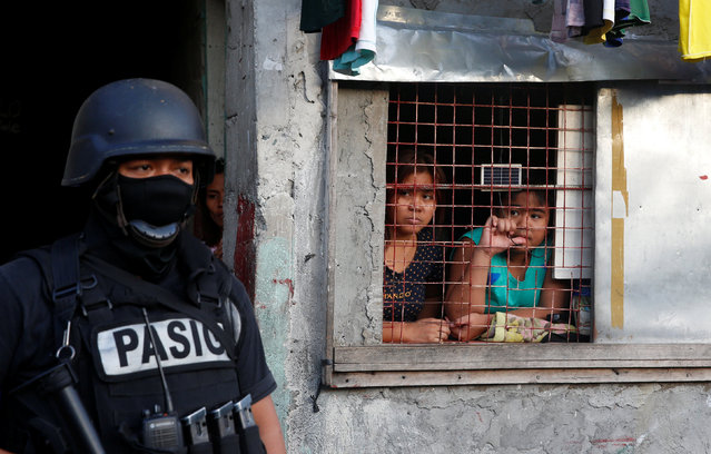 Residents look out from a window during an anti-drugs operation, in Pasig, Metro Manila in the Philippines, November 9, 2016. (Photo by Erik De Castro/Reuters)