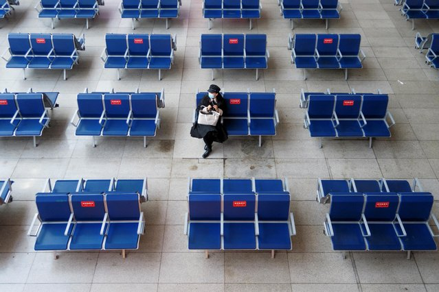 A woman waits in the departure hall of Beijing South Railway station ahead of Lunar New Year celebrations following an outbreak of the coronavirus disease (COVID-19) in Beijing, China, February 10, 2021. (Photo by Thomas Peter/Reuters)