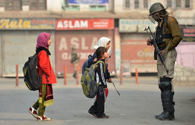 Kashmiri residents walk past Indian paramilitary troopers as they stand guard during curfew and restrictions in downtown Srinagar as the unrest in Kashmir enters 126th day on November 11, 2016. More than 90 civilians have been killed and thousands injured during the latest protests against Indian rule, sparked by the killing on July 8 of a popular rebel leader of Hizbul Mujahieed during a gunfight with Indian soldiers.Kashmir has been divided between India and Pakistan since their independence from British rule in 1947. Both claim the territory in full. (Photo by Tauseef Mustafa/AFP Photo)