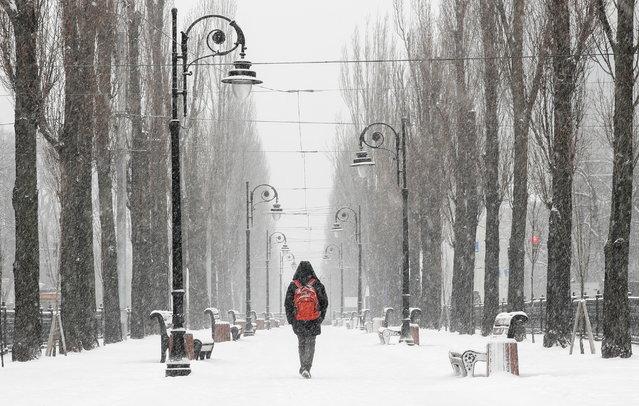 A man walks along a street amid a snowfall in central Kyiv, Ukraine on January 29, 2021. (Photo by Gleb Garanich/Reuters)