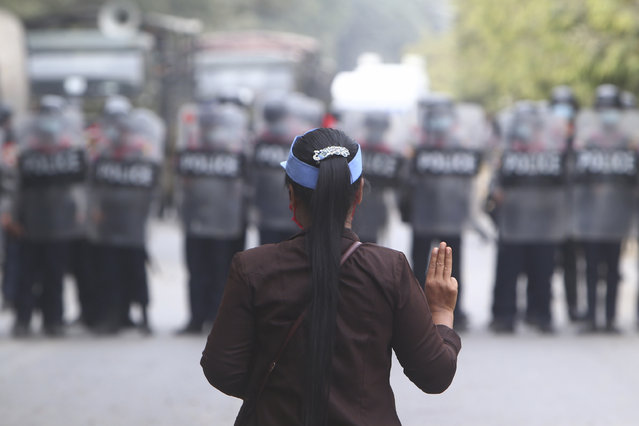A female protester flashes the three-fingered salute in front of police in Mandalay, Myanmar, Saturday, February 20, 2021. (Photo by AP Photo/Stringer)
