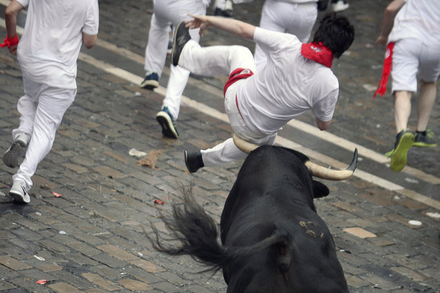 A bull hits a reveller during the first running of the bulls of the San Fermin festival in Pamplona, Spain, July 7, 2018. (Photo by Vincent West/Reuters)