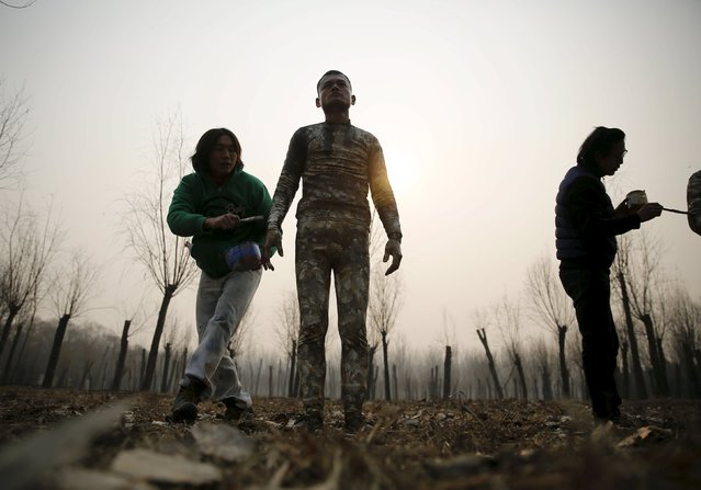 """A staff paints a model with camouflage colours to blend him in with the background for Chinese artist Liu Bolin's artwork """"Dongji"""", or Winter Solstice, on the second day after China's capital Beijing issued its second ever """"red alert"""" for air pollution, in Beijing, China, December 20, 2015. In this artwork, Liu wants to express his concerns about China and its people, including air pollution problem, Liu told Reuters. (Photo by Kim Kyung-Hoon/Reuters)"""