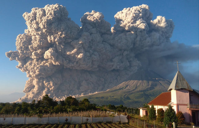 """Mount Sinabung spews volcanic material during an eruption in Karo, North Sumatra, Indonesia, Tuesday, March 2, 2021. The 2,600-metre (8,530-feet) volcano is among more than 120 active volcanoes in Indonesia, which is prone to seismic upheaval due to its location on the Pacific """"Ring of Fire"""", an arc of volcanoes and fault lines encircling the Pacific Basin. (Photo by Mukhsil Lubis/AP Photo)"""
