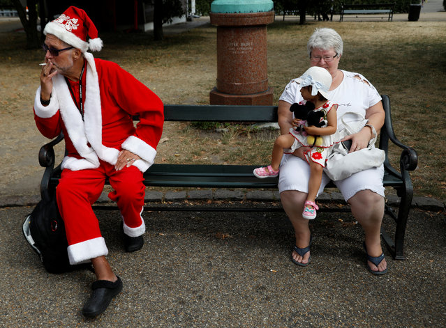 A man dressed as Santa Claus smokes a cigarette before a gathering for the World Santa Claus Congress, an annual event held every summer in Copenhagen, Denmark, July 23, 2018. (Photo by Andrew Kelly/Reuters)