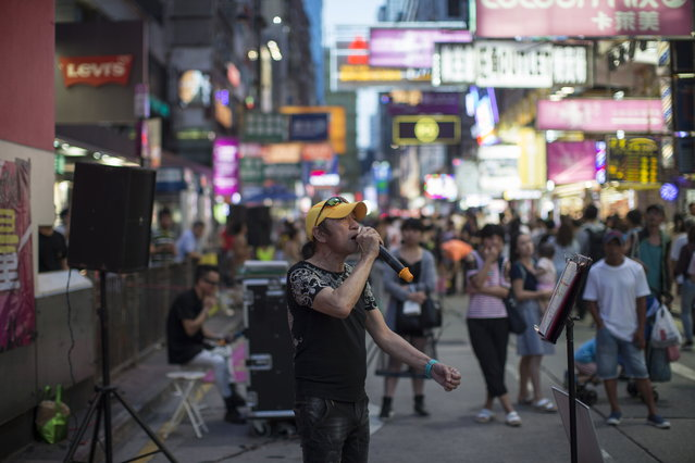 A busker performing in Sai Yeung Choi Street South in Mongkok district, Hong Kong, China, 28 July 2018. (Photo by Jerome Favre/EPA/EFE)