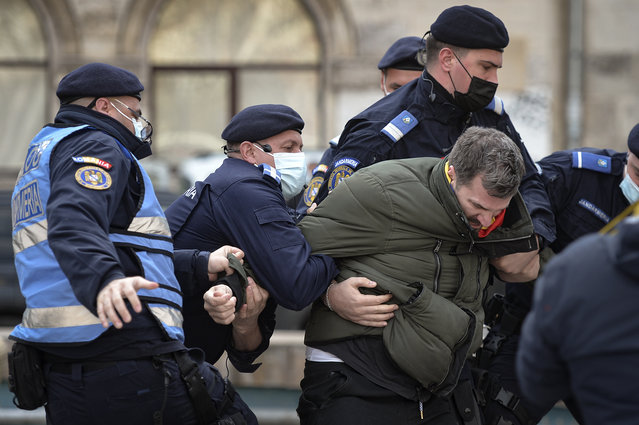 Four Romanian riot police officers struggle to detain a protester against COVID-19 restrictions before people gathered for a rally joined by thousands in Bucharest, Romania, Monday, March 29, 2021. Thousands of anti-restriction protesters took to the streets in several cities across Romania on Monday evening, a day after new restriction measures came into force. (Photo by Alexandru Dobre/AP Photo)