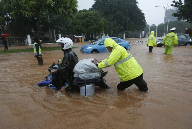 A policeman helps a motorist on flooded street outside the Presidential Palace after heavy seasonal rains flooded parts of Jakarta February 9, 2015. (Photo by Darren Whiteside/Reuters)