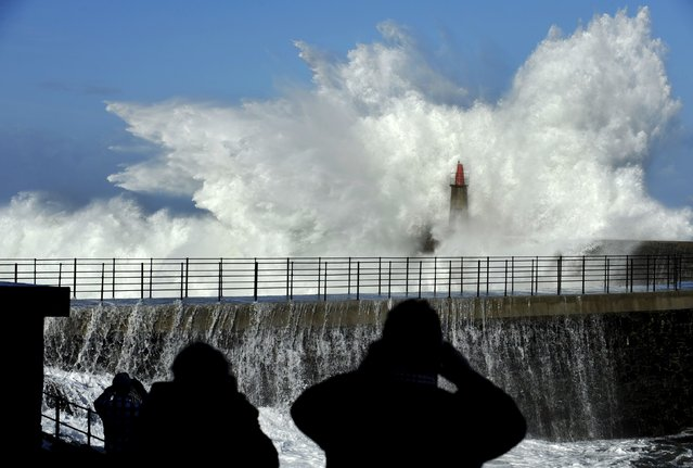People take pictures of huge waves crash on the Viavelez seafront in the northern Spanish region of Asturias January 2, 2016. (Photo by Eloy Alonso/Reuters)