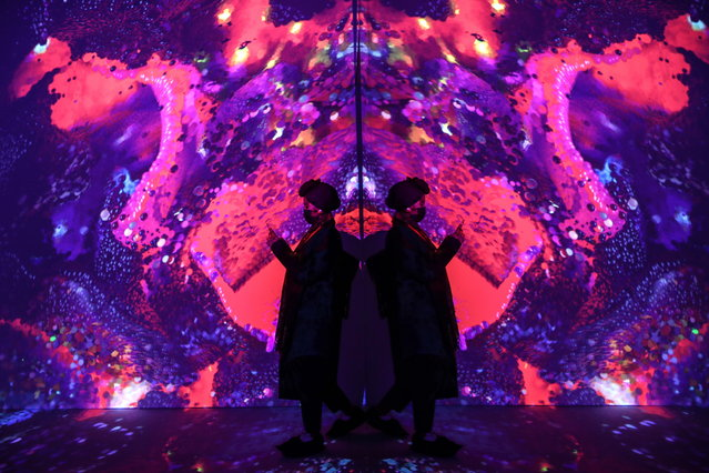 "People visit the art installation ""Machine Memories: Space"" by Turkish artist Refik Anadol in the exhibition at Pilevneli Art Gallery in Istanbul, Turkey, 22 March 2021. The exhibition runs until 25 April. (Photo by Sedat Suna/EPA/EFE)"