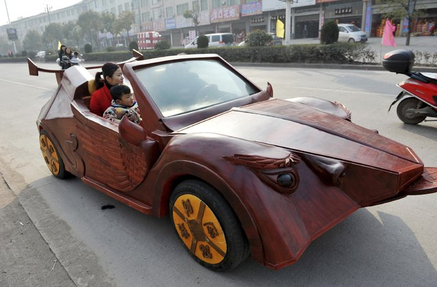 Yu Jietao (C), 26-year-old wood carver, drives his homemade wooden car along a street with his family, in Guangfeng county of Shangrao, Jiangxi province February 9, 2015. Yu spent over 100,000 yuan ($16,010) to build the wooden vehicle, which is approximately 4m-long (13.12 ft), 1.5m-wide (4.92 ft) and 1.5m-high. The car can travel as fast as 30 km (18.6 miles) per hour, local media reported. (Photo by Reuters/Stringer)
