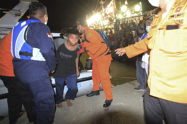 Rescuers assist one of the survivors of a ship collision, center, upon his arrival at a port in Indramayu, West java, Indonesia, Sunday, April 4, 2021. The collision between a cargo ship and a fishing boat left a number of people missing off Indonesia's main island of Java, officials said Sunday. (Photo by Panji Wisnu/AP Photo)