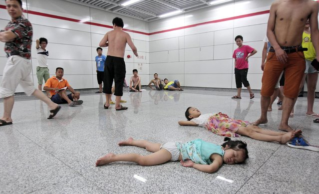 Children sleep on the floor of the Qiaosi subway station in Hangzhou, Zhejiang province July 25, 2013. More than 600 people cooled off inside the subway station as temperatures in the city hit a high of 40 degrees Centigrade during a regional power outage on Thursday. (Photo by Reuters/Stringer)