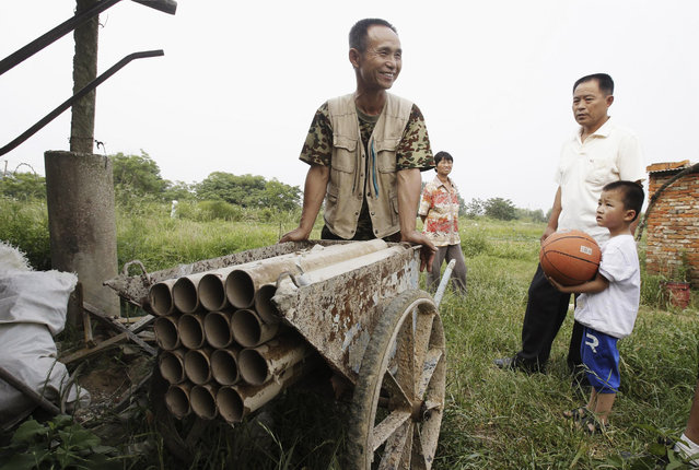 Chinese farmer Yang Youde pushes his homemade cannon near his farmland on the outskirts of Wuhan, Hubei province June 6, 2010. Yang's cannon, which is made out of a wheelbarrow, pipes and firing rockets, is used to defend his fields against property developers who wants his land. (Photo by Reuters/Stringer)