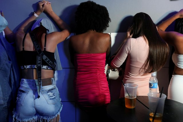 Women hide their faces in a night club during a civil police operation tackling COVID-19 restrictions violations, amid a rise in coronavirus disease cases and deaths in Sao Paulo, Brazil on April 2, 2021. (Photo by Amanda Perobelli/Reuters)