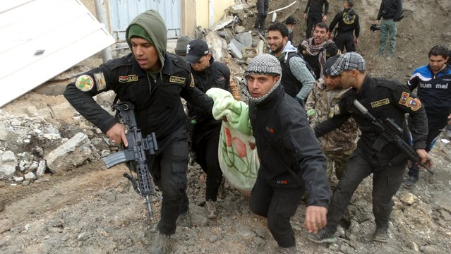 Iraqi security forces and pro-government Sunni tribal fighters evacuate a badly injured man in Ramadi city, Iraq January 4, 2016. (Photo by Reuters/Stringer)