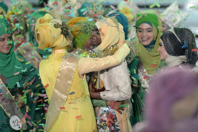 The newly crowned the Muslimah World 2013 Obabiyi Aishah Ajibola (C-R) of Nigeria is congratulated by contestants during the Muslimah World competition in Jakarta on September 18, 2013. (Photo by Adek Berry/AFP Photo)