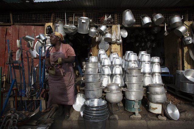 A woman stands by a local shop that sells dishes and other utensils made from recycled metal cut from oil barrels in Kamukunji, Nairobi on February 16, 2015. (Photo by Siegfried Modola/Reuters)