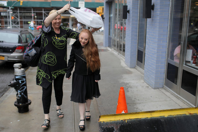 Rosanne Stuart attempts to cover her daughter, model Madeline Stuart, from falling rain as they walk to a show during New York Fashion Week in New York City, U.S., September 9, 2018. (Photo by Andrew Kelly/Reuters)