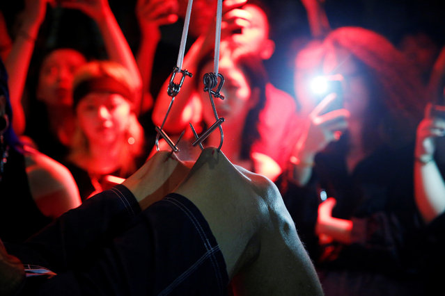 """Spectators watch as Viktor Liu is suspended from hooks pierced through his skin by professional body artist Wei Yilaien at a bar in Shanghai, China on September 16, 2018. Liu said his first experience hanging from hooks thrust into his skin was three years ago. It was a hasty decision made on a night when Liu was drunk, he said, but he now takes up the challenge once a year. """"The process is very calming, as if I had separated from the world and entered a different space altogether which was wonderful and unreal"""", Liu said. However, he admitted it comes with a price. """"After the suspension, it felt painful. Very painful"""", Liu said. (Photo by Aly Song/Reuters)"""