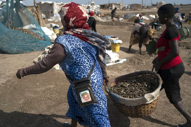 Women carry buckets filled with processed fish on Bargny beach, some 35 kilometers (22 miles) east of Dakar, Senegal, Sunday April 25, 2021. (Photo by Leo Correa/AP Photo)
