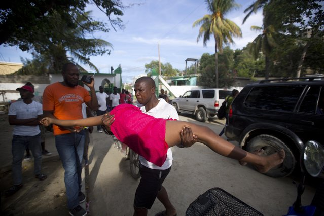 A woman overcome by emotion after an aftershock hit the area, is carried by a relative to the general hospital in Port-de-Paix, Haiti, Sunday, October 7, 2018. A magnitude 5.2 aftershock struck Haiti on Sunday, even as survivors of the previous day's temblor were sifting through the rubble of their cinderblock homes. The death toll stood at 12, with fears it could rise. (Photo by Dieu Nalio Chery/AP Photo)