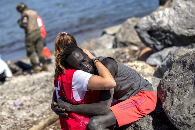 A migrant is comforted by a member of the Spanish Red Cross near the border of Morocco and Spain, at the Spanish enclave of Ceuta, on Tuesday, May 18, 2021. (Photo by Bernat Armangue/AP Photo)