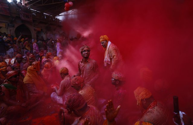 FILE - In this Friday, Feb. 27, 2015 file photo, Hindu men from the village of Nandgaon throw colored powder at each other before joining a procession for the Lathmar Holi festival at the legendary hometown of Radha, consort of Hindu God Krishna, in Barsana, 115 kilometers (71 miles) from New Delhi, India. During Lathmar Holi the women of Barsana beat the men from Nandgaon, the hometown of Krishna, with wooden sticks in response to their teasing. (AP Photo/Saurabh Das, File)