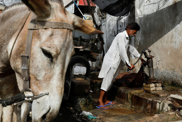 Mohammad Ramzan, 60, a traditional goatskin water carrier also known as a mashki, fills a bag with water from a handpump to deliver to nearby homes during the fasting month of Ramadan, as the outbreak of the coronavirus disease (COVID-19) continues, in Karachi, Pakistan on April 23, 2021. (Photo by Akhtar Soomro/Reuters)