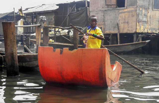 A Nigerian pupil rows to school using a makeshift canoe out of half a plastic barrel as he makes his way to a floating school in Makoko, Lagos, Nigeria 09 March 2015. The school built for children of Makoko riverine  community who live in homes over the water was supported by the United Nations Development Program (UNDP).  EPA/STR
