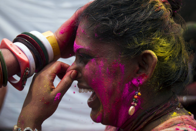 An Indian woman covers her nose as her friend smears her face with colored powder during Holi in Kuala Lumpur, Malaysia on Saturday, March 21, 2015. (Photo by Joshua Paul/AP Photo)