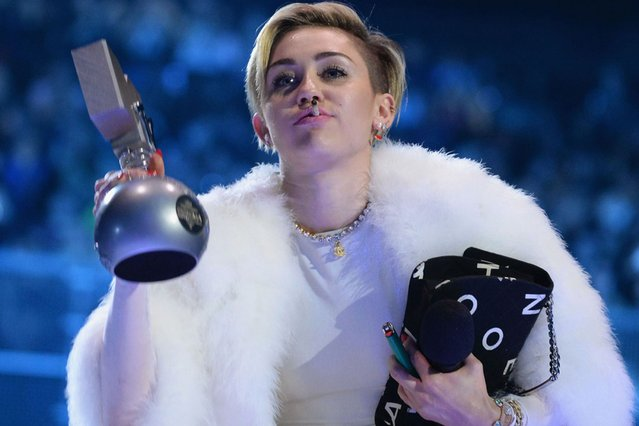 Miley Cyrus smokes what appears to be a joint as accepts her award at the MTV EMA's 2013. (Photo by Jeff Kravitz/FilmMagic)