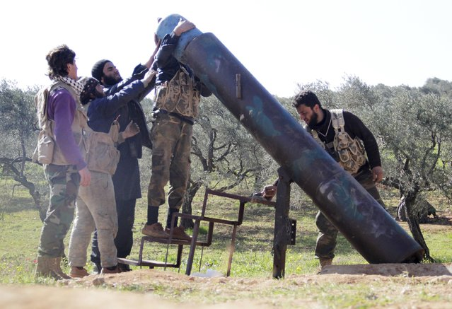 Rebel fighters from Suqour al-Sham Brigade prepare to launch a locally made shell towards forces loyal to Syria's president Bashar Al-Assad who are stationed in checkpoints surrounding the city of Idlib March 23, 2015. (Photo by Mohamad Bayoush/Reuters)