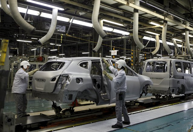 Employees of Nissan Motor Co. work on the assembly line at the company's Kyushu plant in Kanda town, Fukuoka Prefecture, Japan, in this July 9, 2015 file photo. Japan is expected to report manufacturing PMI numbers this week. (Photo by Maki Shiraki/Reuters)