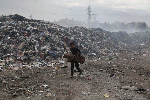 A boy carries boxes as he walks along a garbage filled area in Jisr al-Hajj in Aleppo May 14, 2015. (Photo by Hosam Katan/Reuters)