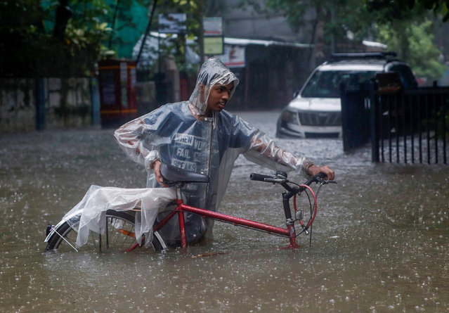 A man wades through a waterlogged street with a bicycle after heavy rainfall in Mumbai, India, July 16, 2021. (Photo by Francis Mascarenhas/Reuters)