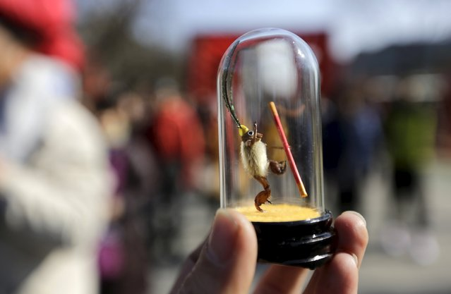 """A visitor displays a """"Maohou"""" at a Spring Festival temple fair on the second day of the Chinese Lunar New Year of the Monkey in Beijing, China, February 9, 2016. """"Maohou"""", which means hairy monkey in Chinese, is a traditional art form in Beijing that dates back to the Qing Dynasty and requires only the use of cicada slough and magnolia buds to form miniature sculptures. (Photo by Jason Lee/Reuters)"""