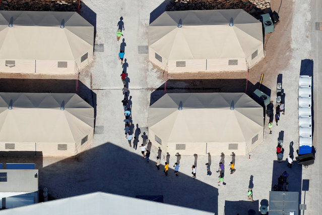 """Immigrant children, many of whom have been separated from their parents under a """"zero tolerance"""" policy by the Trump administration, are shown walking in single file between tents in their compound next to the Mexican border in Tornillo, Texas, June 18, 2018. (Photo by Mike Blake/Reuters)"""