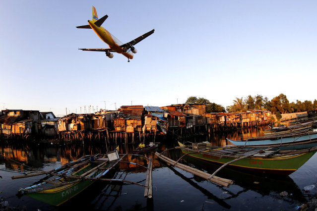 Fishing boats take shellter as an airplane flies over at a fishing village in Paranaque city, south of Manila, Philippines, 03 April 2015. Philippine authorities prepared to evacuate thousands of people ahead of possible tidal surges, flash floods and landslides from an incoming typhoon. (Photo by Francis R. Malasig/EPA)