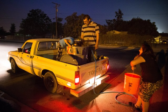 Macario Beltran, 41, a mechanic whose family's well has run dry, fills containers in his truck with water from the fire station, with his daughters Abigail, 6, (L) and Denika, 10, in Porterville, October 14, 2014. (Photo by Lucy Nicholson/Reuters)