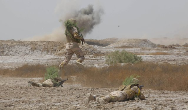 Iraqi security forces demonstrate their skills while smoke rises from a mock bomb as part of military training in Jurf al-Sakhar, Iraq April 9, 2015. (Photo by Alaa Al-Marjani/Reuters)