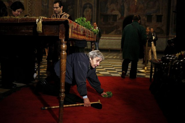 A worshipper passes under a table, where the Bible is placed, as a mark of respect to Jesus Christ during a Good Friday mass at Alexander Nevski cathedral in Sofia April 10, 2015. Bulgaria and other Eastern Orthodox countries celebrate Easter this weekend. (Photo by Stoyan Nenov/Reuters)