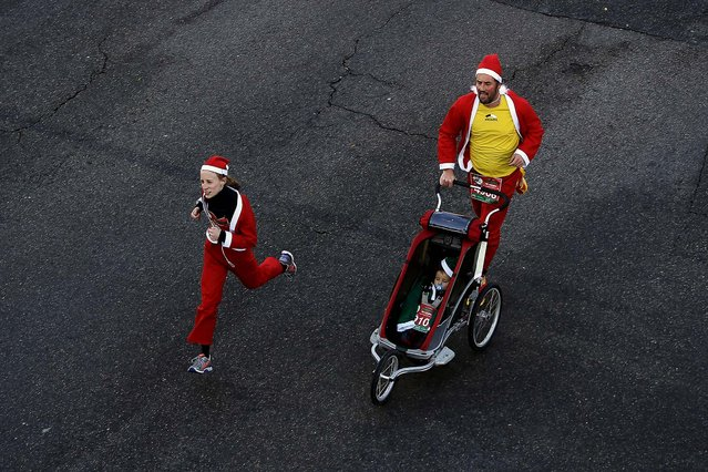 """A couple dressed as Santa Claus run carrying a baby during a Marathon in Madrid. Around 6,000 people dressed as Santa Claus and his elves ran a """"mini-marathon"""" through the streets to promote festive cheer as the country tries to emerge from a two-year recession. (Photo by Andres Kudacki/Associated Press)"""