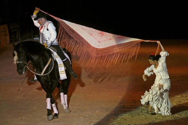 An Andalusian man and woman in traditional Sevillana garb perform with a horse during the Sacab Andalusian Horse Show in Coin, southern Spain, April 12, 2015. (Photo by Jon Nazca/Reuters)